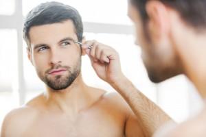 Man tweezing his eye brows