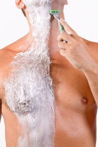 Man shaving his hairy chest
